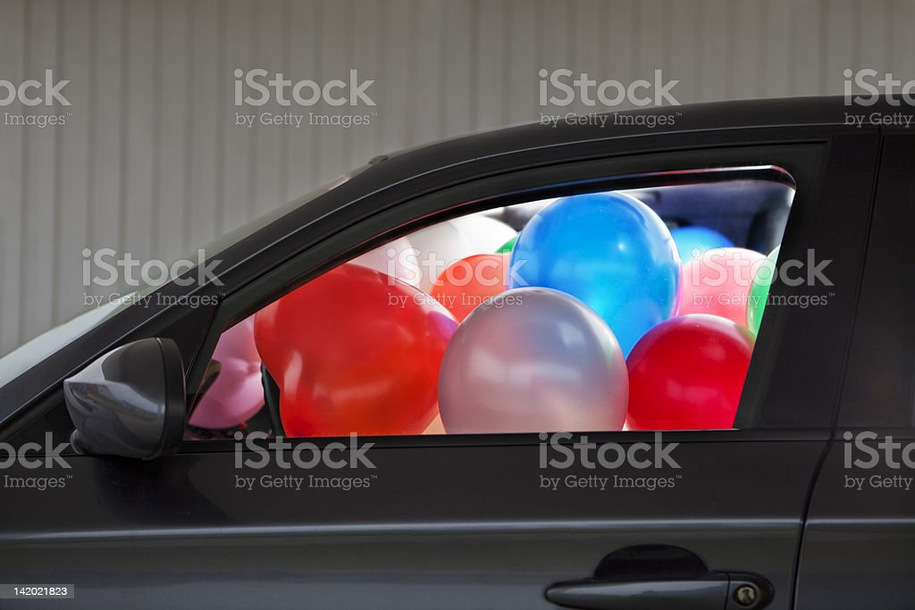 Car filled with colorful balloons stock photo