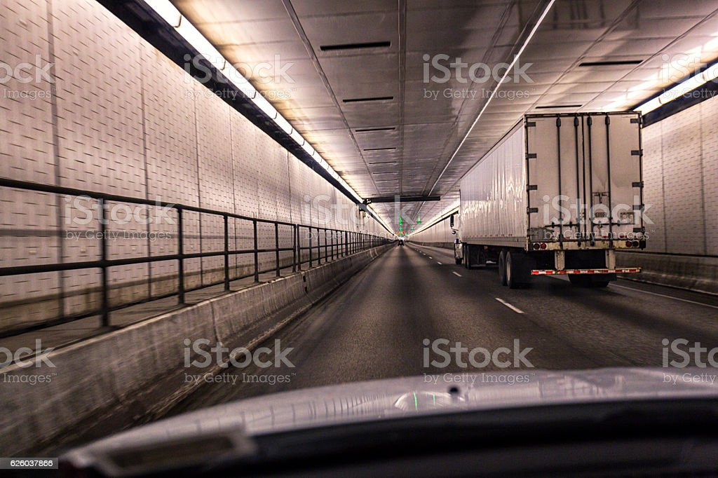 Car Following Trailer Truck Inside Pennsylvania Turnpike Lehigh Road Tunnel stock photo