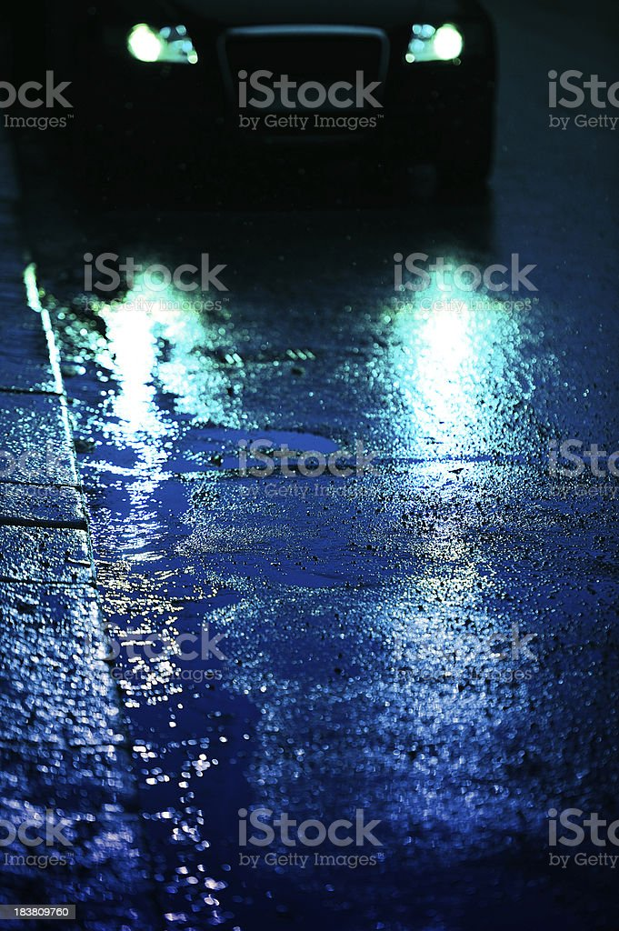 Car front light reflecting in rain wet asphalt royalty-free stock photo