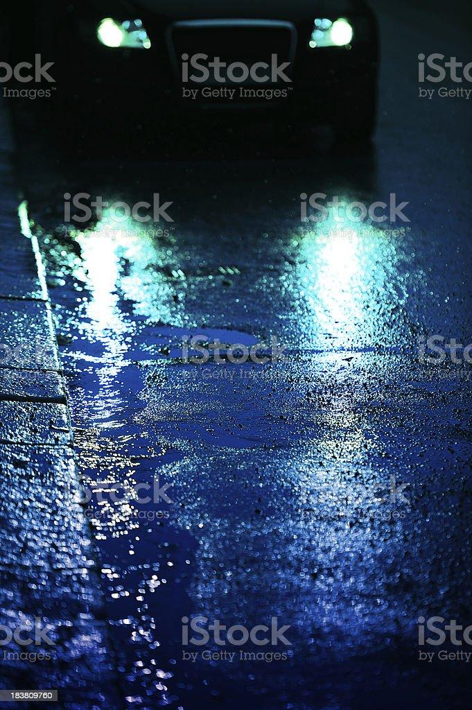 Car front light reflecting in rain wet asphalt stock photo