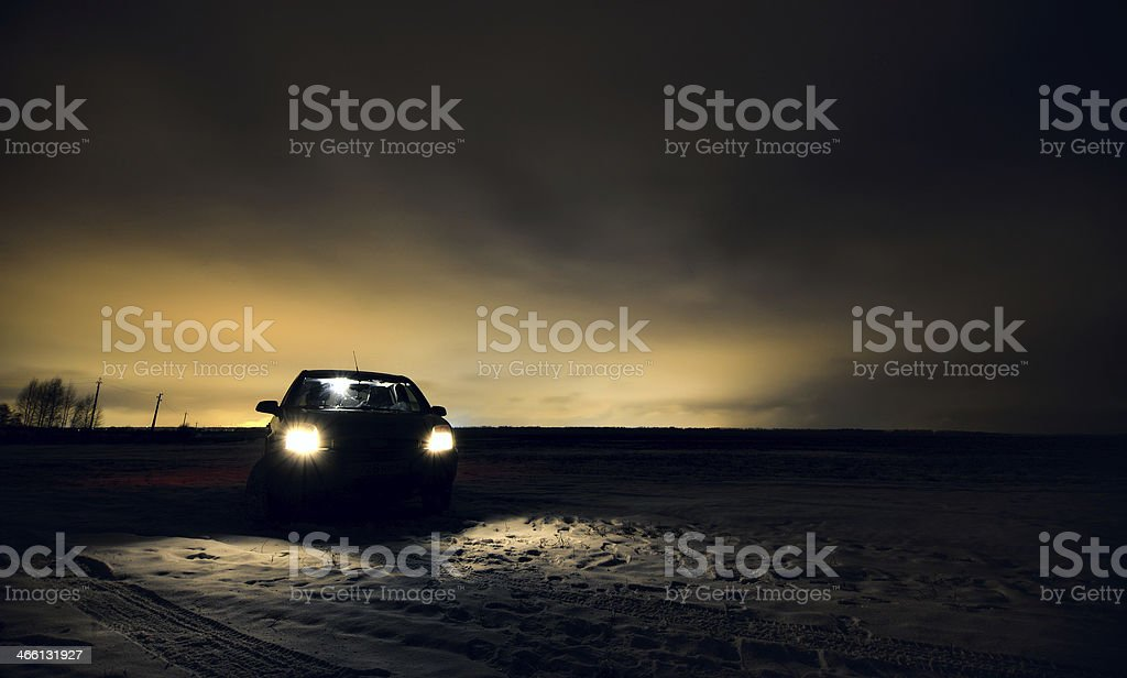 Car headlights turned in night field stock photo