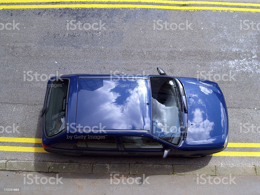 Car illegally parked on double yellow lines from above stock photo