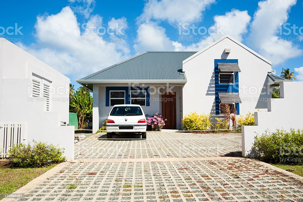 Car in a driveway at a white Caribbean style home stock photo
