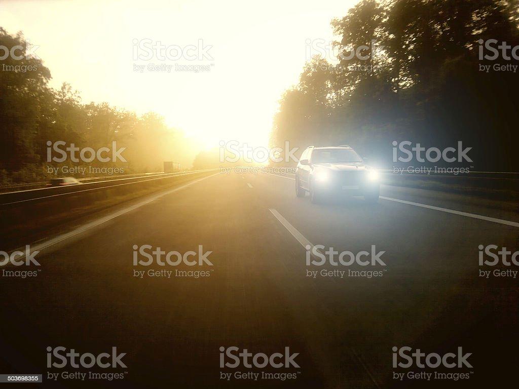 car in morning light on highway stock photo