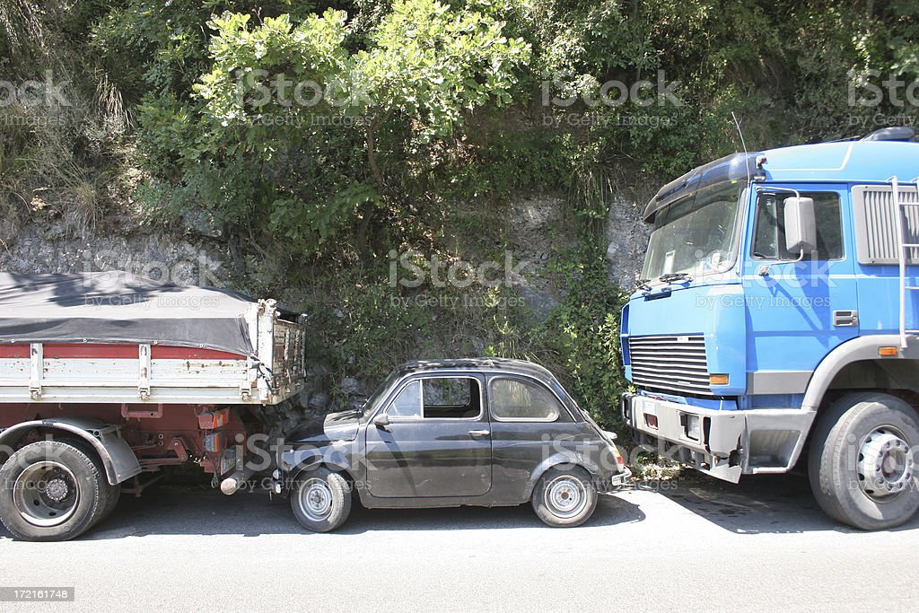 Parked automobile trapped by two trucks on and Italian side street.