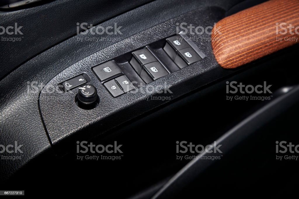 Car interior details of door handle with windows controls and adjustments. stock photo