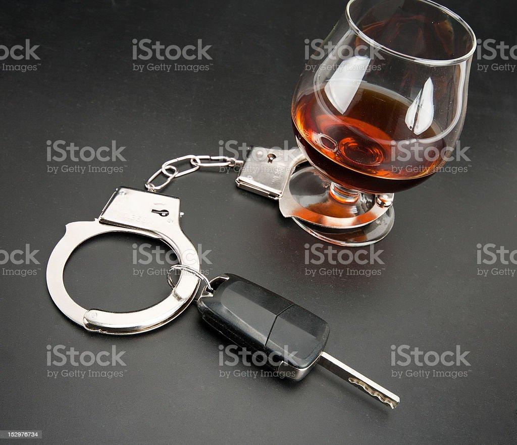 Car key locked to glass of alcohol stock photo