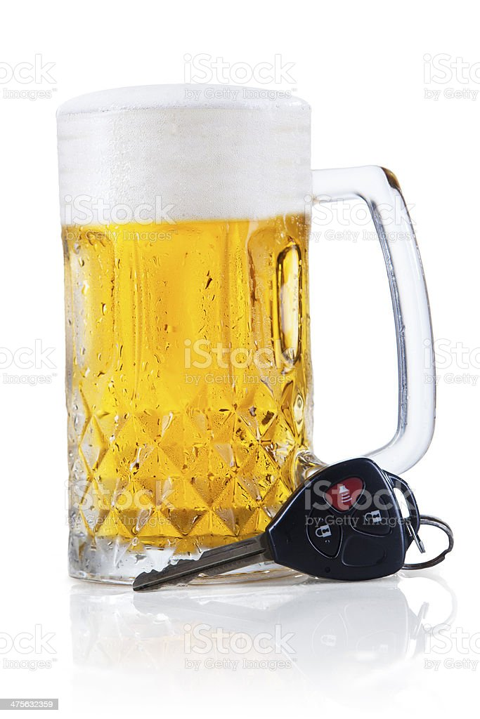Car key lying next to a full glass of beer stock photo