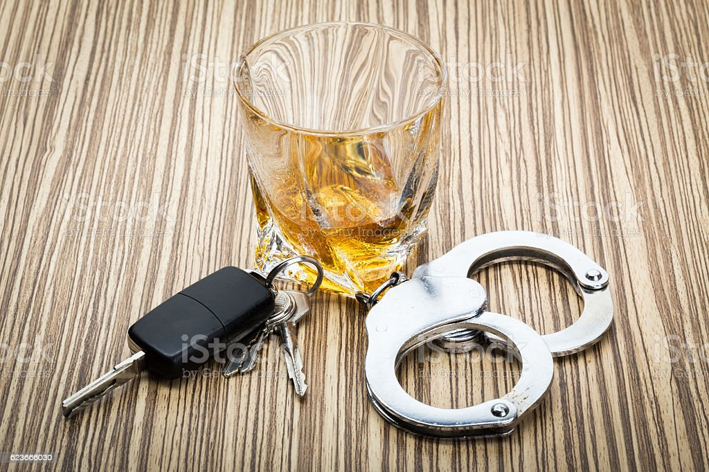 Car key on the bar with alcohol and handcuffs stock photo