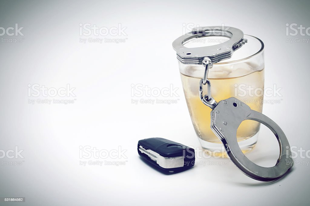 Car key with glass of whiskey and handcuffs stock photo