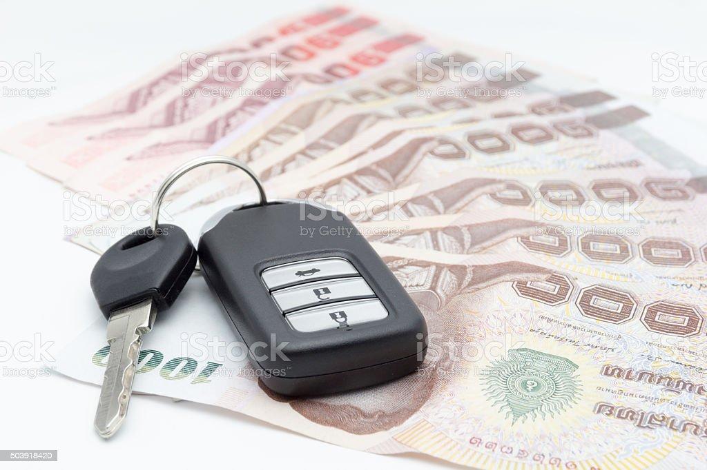 car keys and money baht on a white background stock photo