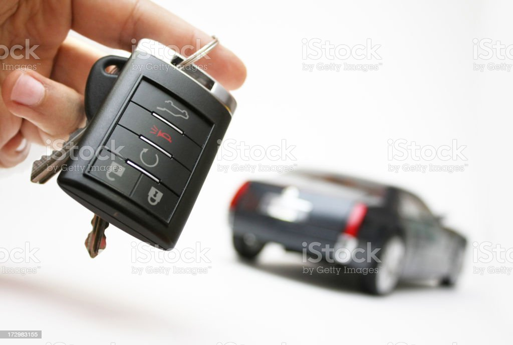 Car keys in a hand with an unfocused car in the background stock photo