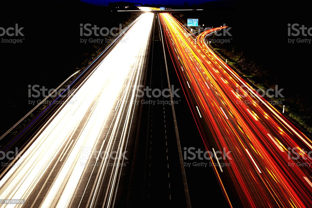 Car light trails on highway at night stock photo