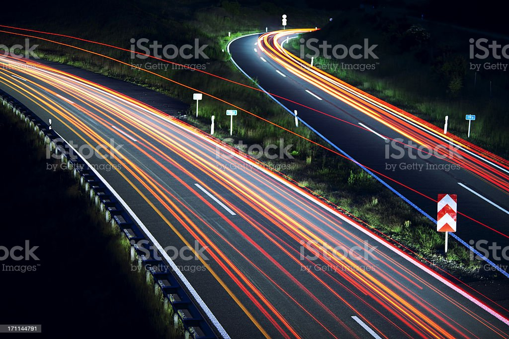 Car light trails on highway junction at night stock photo