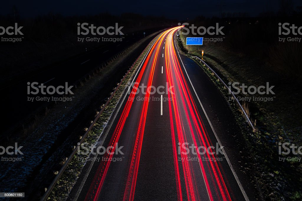 Car light trails with blue road sign, long exposure stock photo
