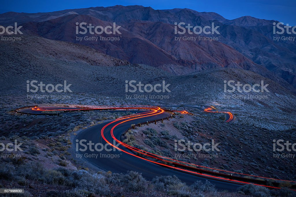 Car lights on a curvy road in darkness stock photo