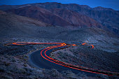 Car lights on a curvy road in darkness