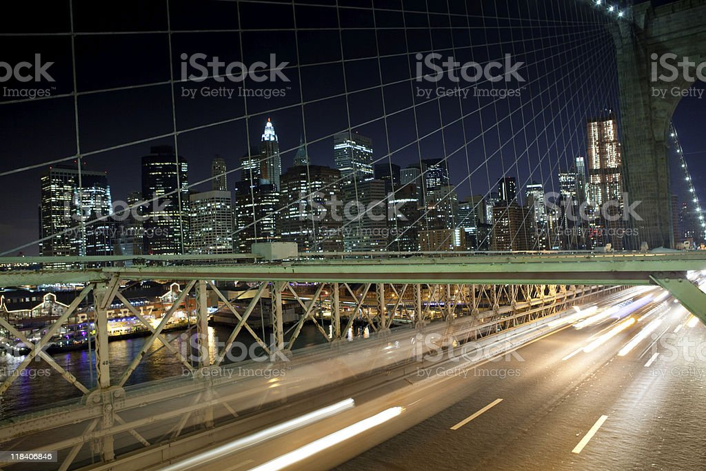 Car lights on Brooklyn bridge with Manhattan in background stock photo