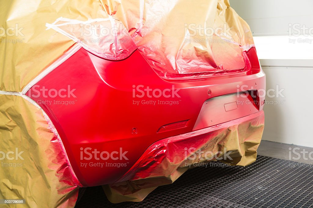 Car masked with tape and paper sprayed with red paint stock photo