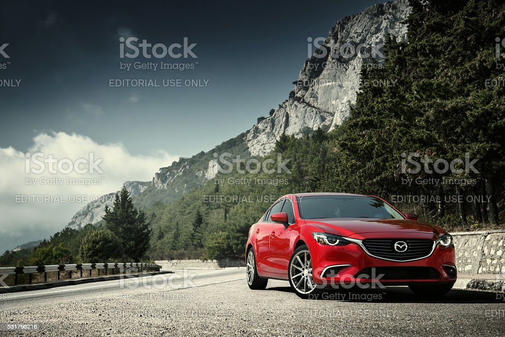Car Mazda standing on the road near mountains at daytime stock photo