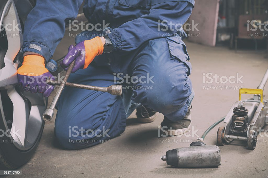 Car mechanic changing tire in the service - shop. stock photo