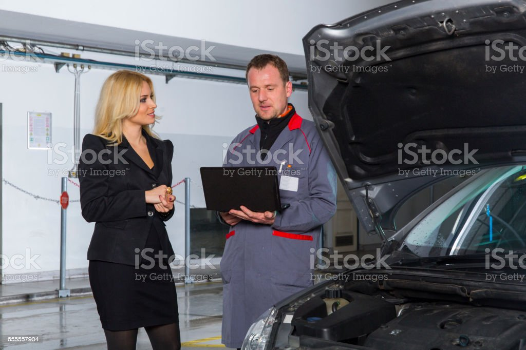 Car mechanic checking engine with computer...cute customer observing him stock photo
