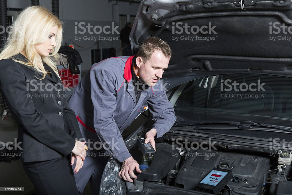 Car mechanic checking engine...cute customer observing him royalty-free stock photo