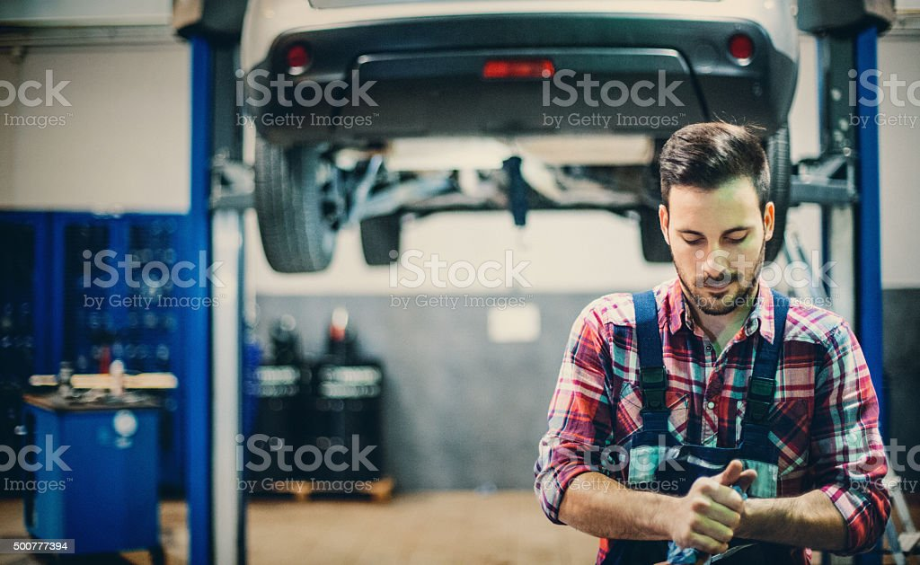 Car mechanic cleaning his hands after work. stock photo