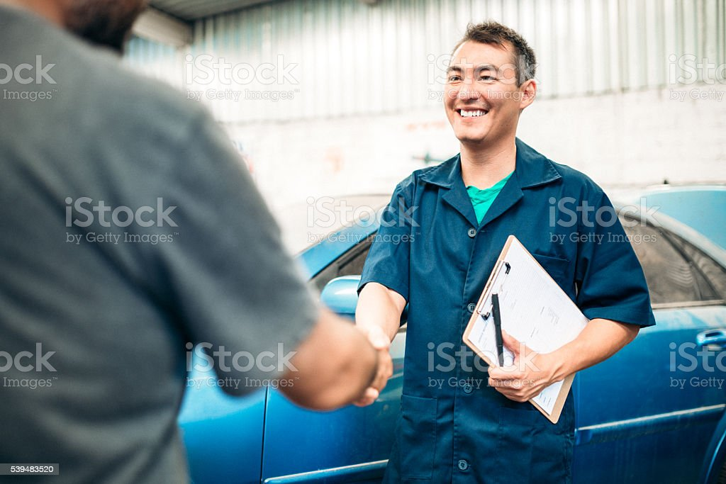 Car mechanic handshakes customer stock photo