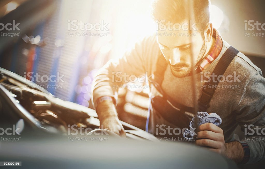 Car mechanic inspecting engine during service procedure. stock photo