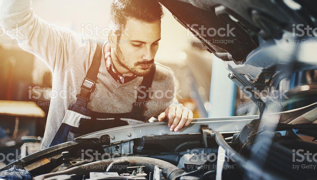 Car mechanic inspecting engine during service procedure. stock photo