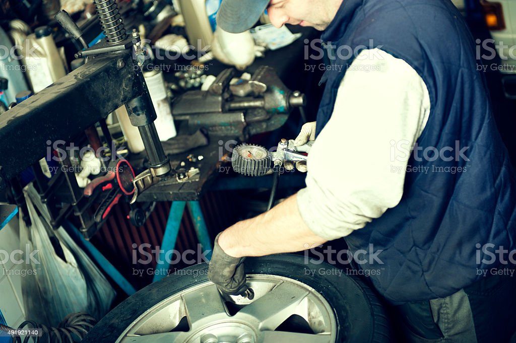 Car mechanic is checking tire air pressure stock photo