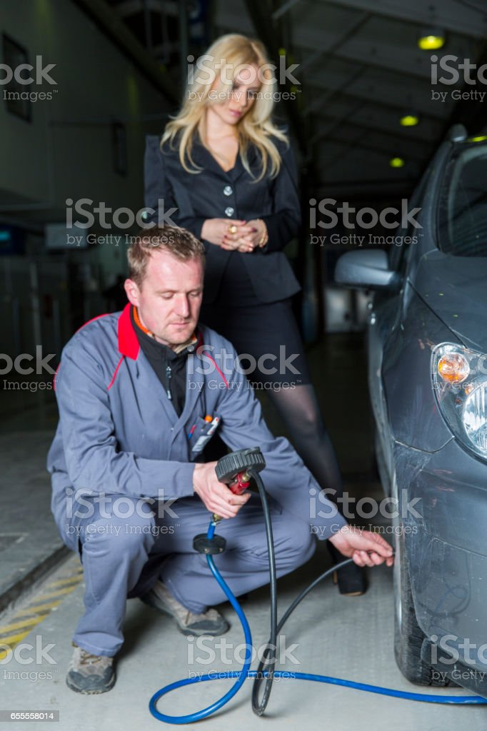 Car mechanic is checking tire pressure....cute customer observing him stock photo