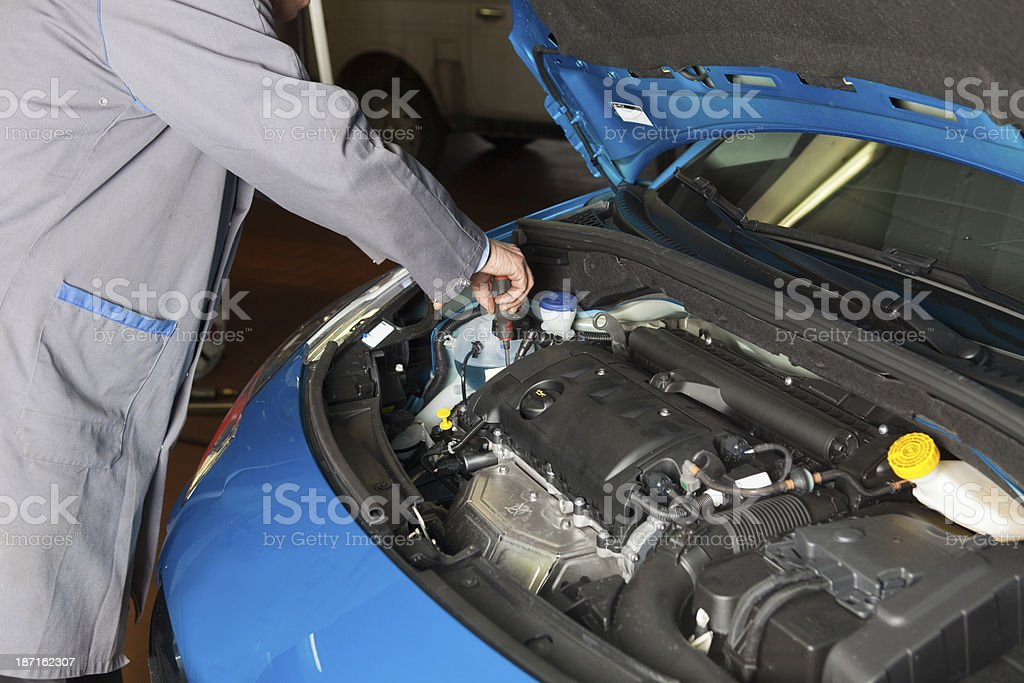 Car mechanic is fixing engine in an auto repair shop royalty-free stock photo