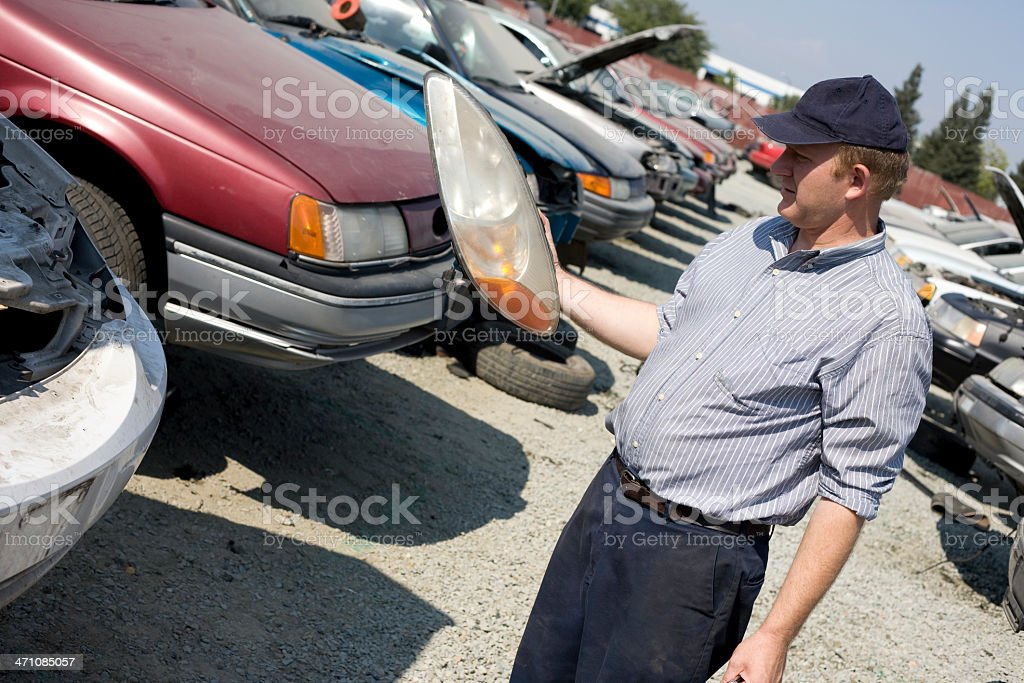 Car mechanic looking at a used headlight royalty-free stock photo
