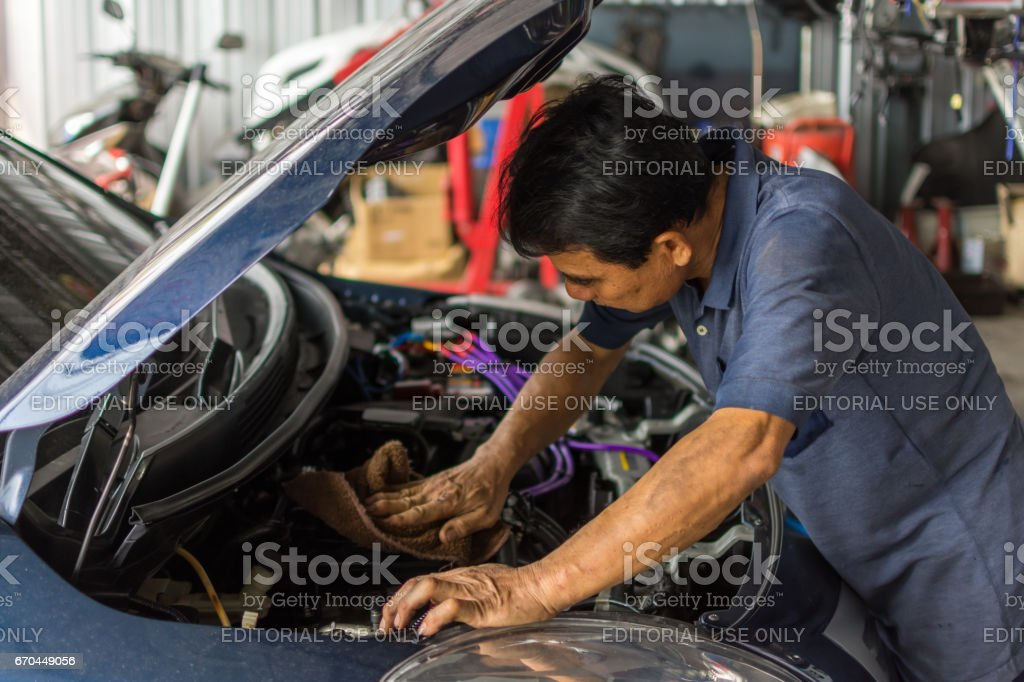 Unidentified car mechanic or serviceman checking a car engine for fix...
