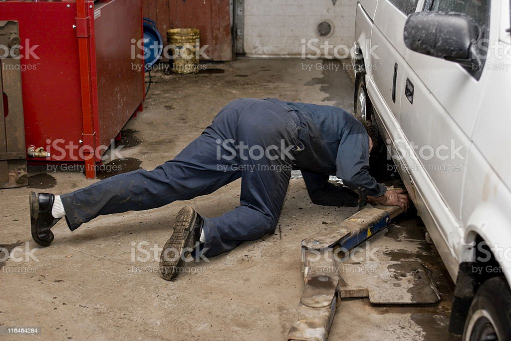 Car Mechanic positioning vehicle on a lift. royalty-free stock photo