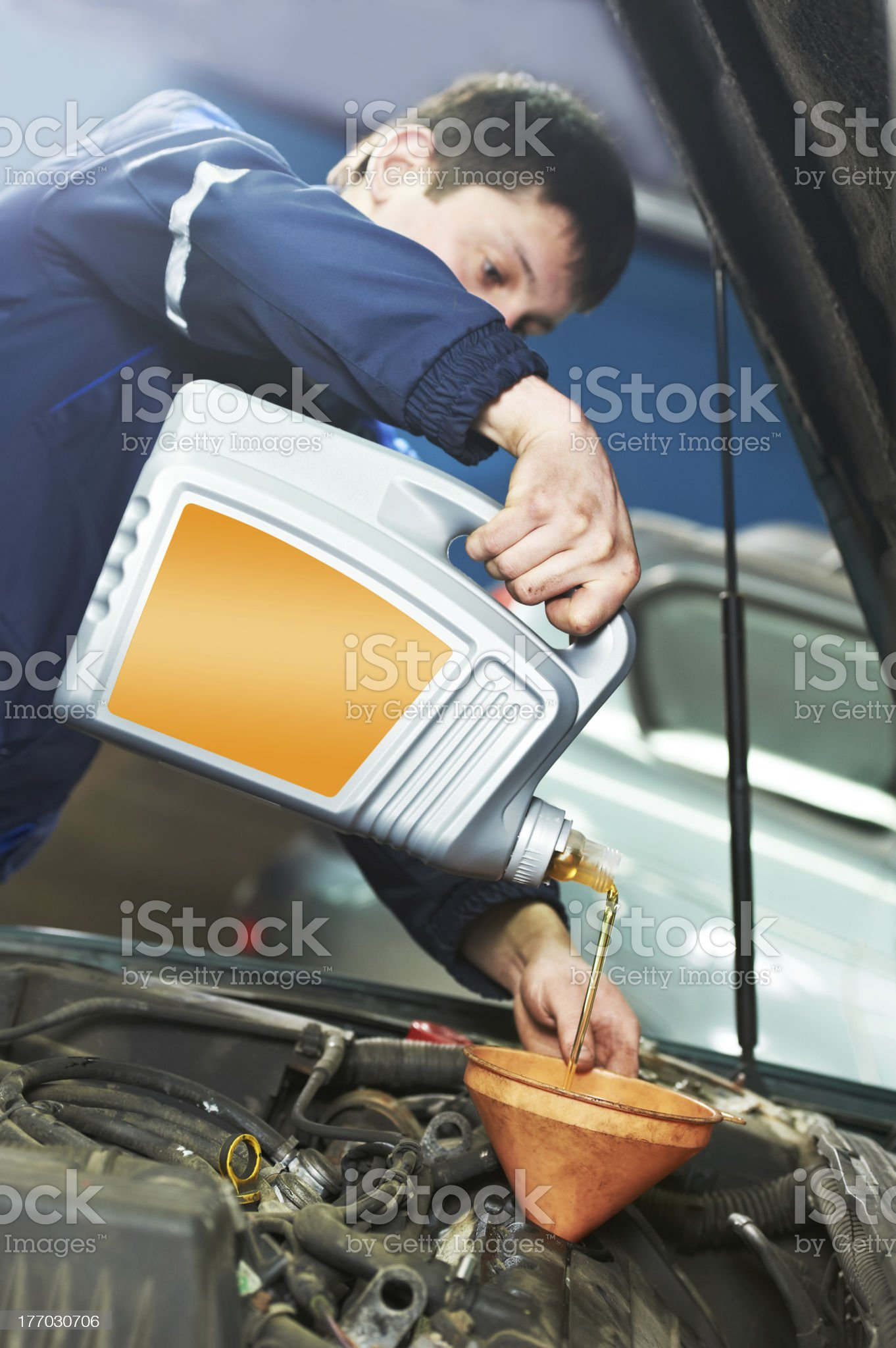 car mechanic pouring oil into motor engine royalty-free stock photo