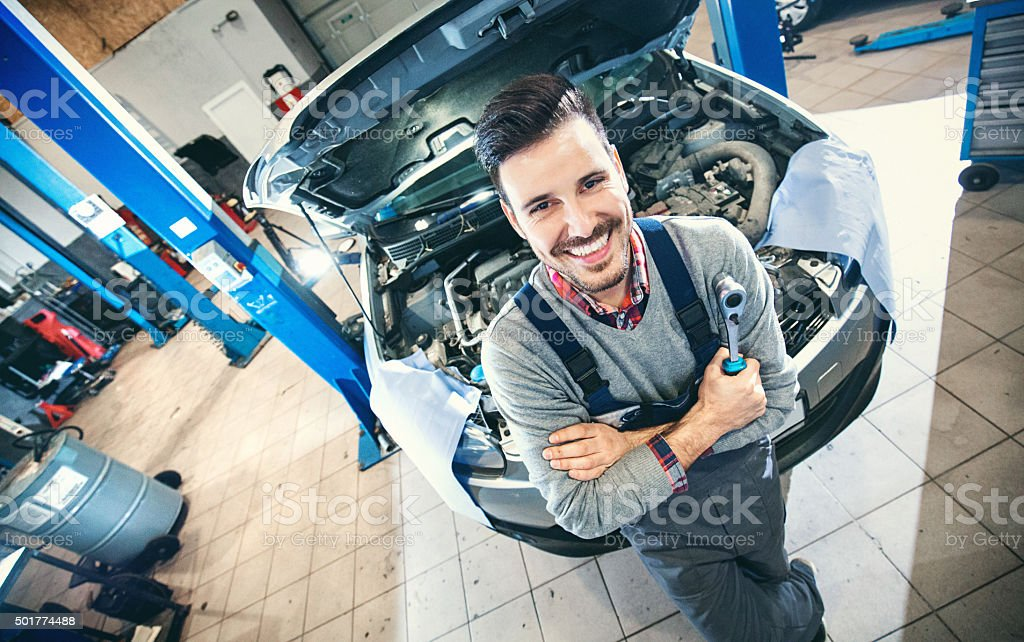 Car mechanic proudly posing. stock photo
