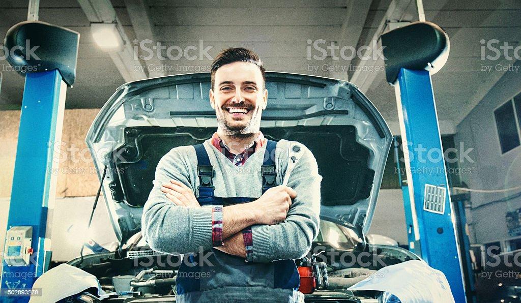 Car mechanic proudly posing. stock photo