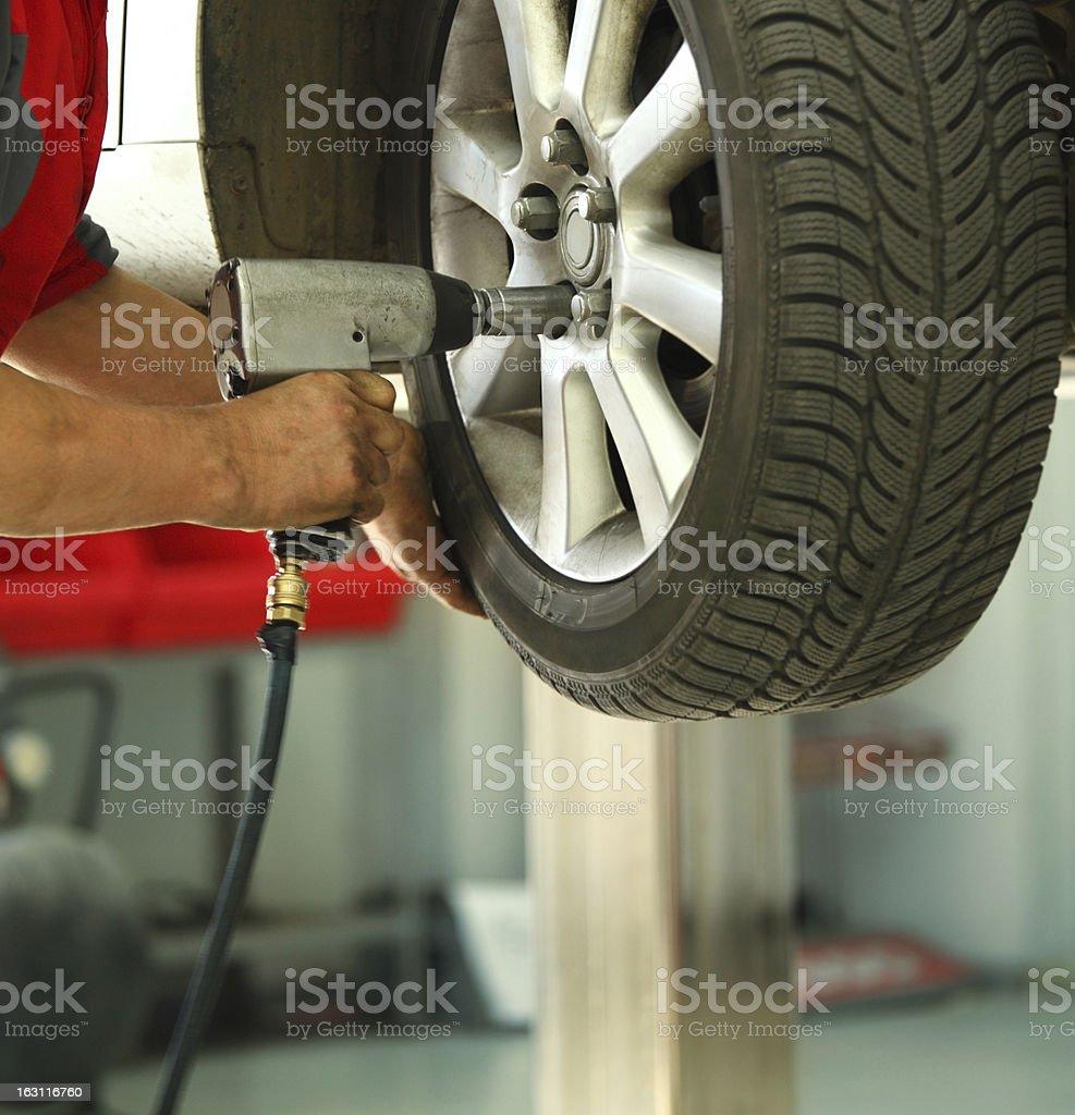 Car mechanic replacing a wheel. stock photo