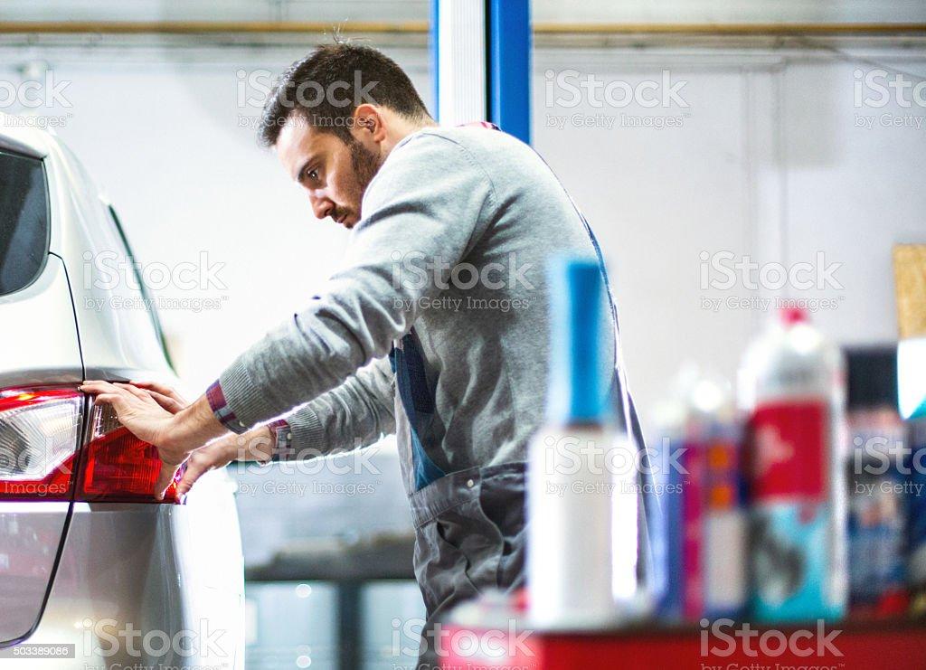 Car mechanic replacing tail light on a vehicle. stock photo