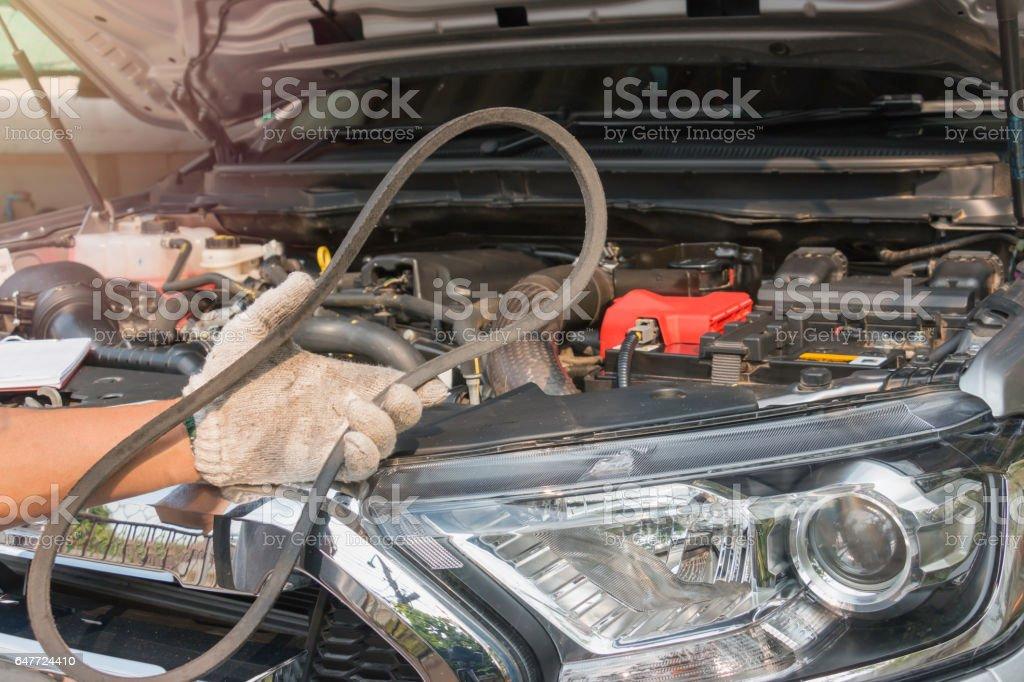 Car mechanic replacing timing belt stock photo