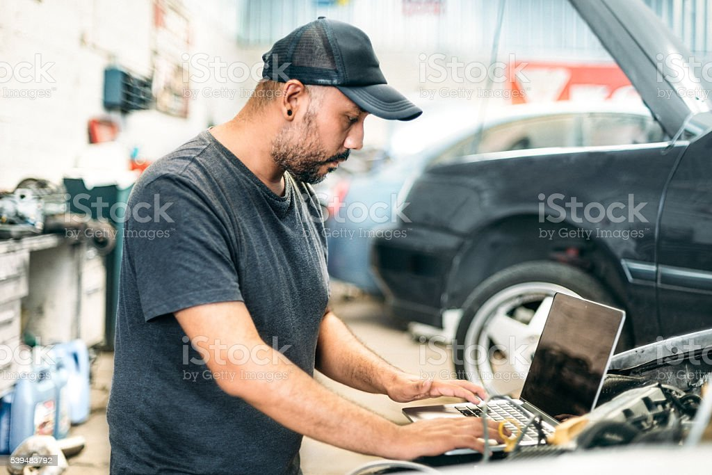 Car mechanic using computer in auto repair shop stock photo