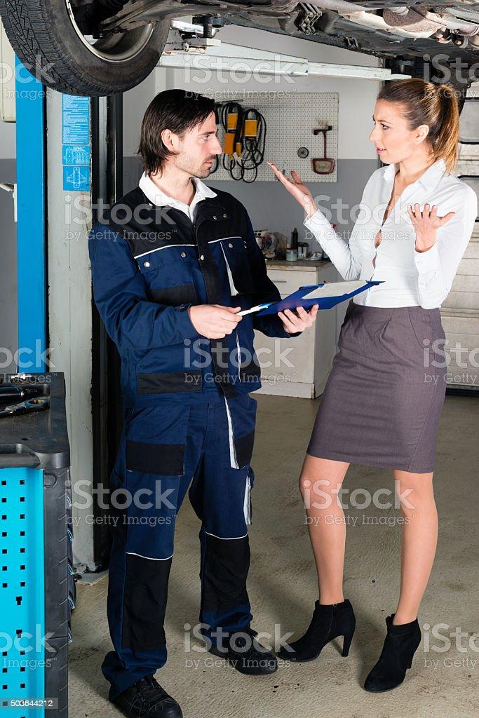 Car mechanic with angry female customer stock photo