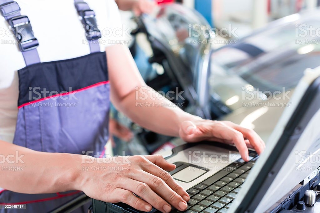 Car mechanic with diagnosis tool in auto workshop stock photo