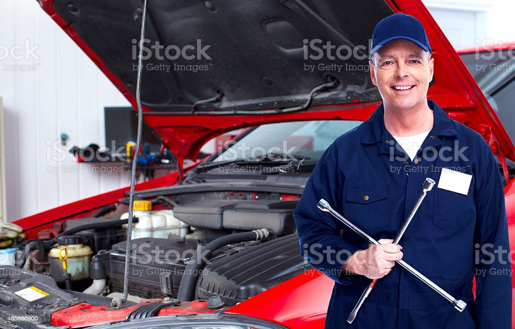 Car mechanic  with tire wrench. stock photo