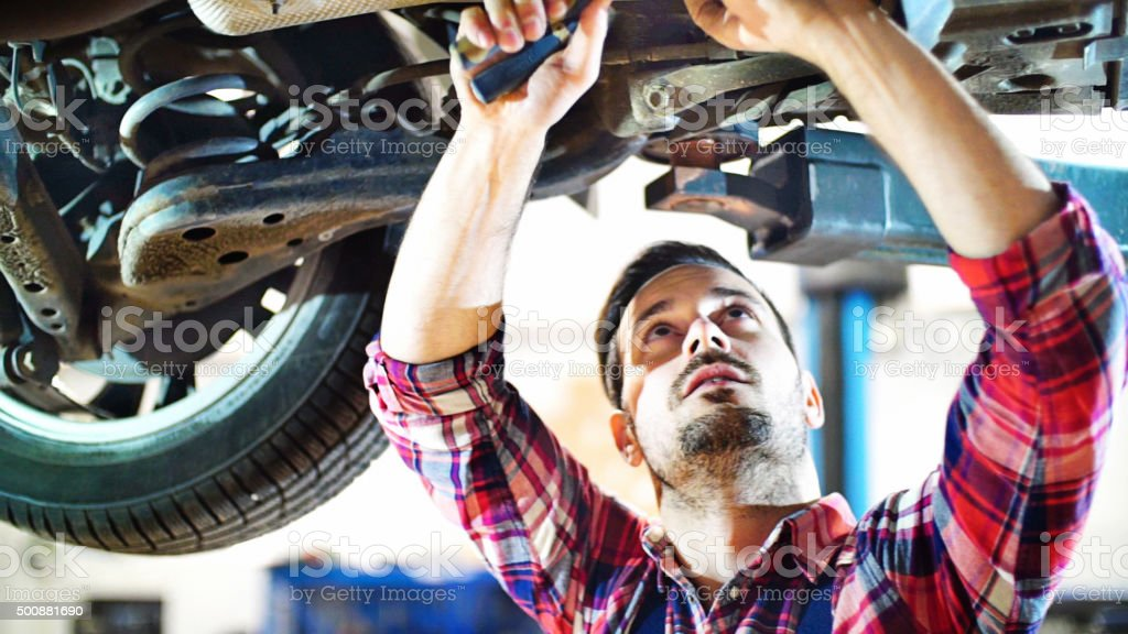 Car mechanic working under a vehicle at workshop. stock photo