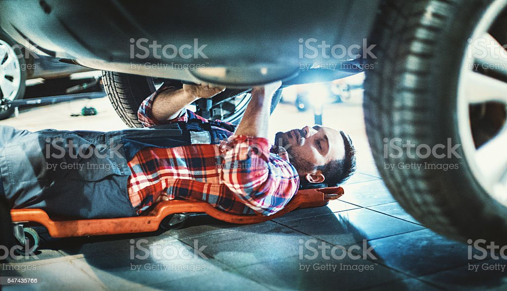 Car mechanic working under a vehicle. stock photo