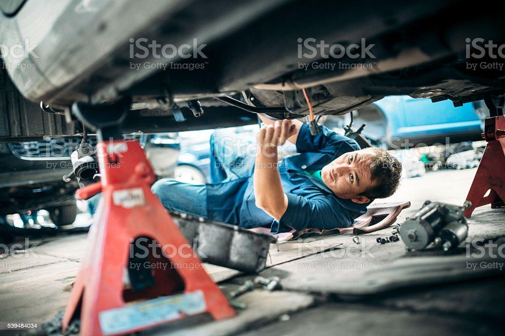 Car Mechanic Working Under Vehicle stock photo